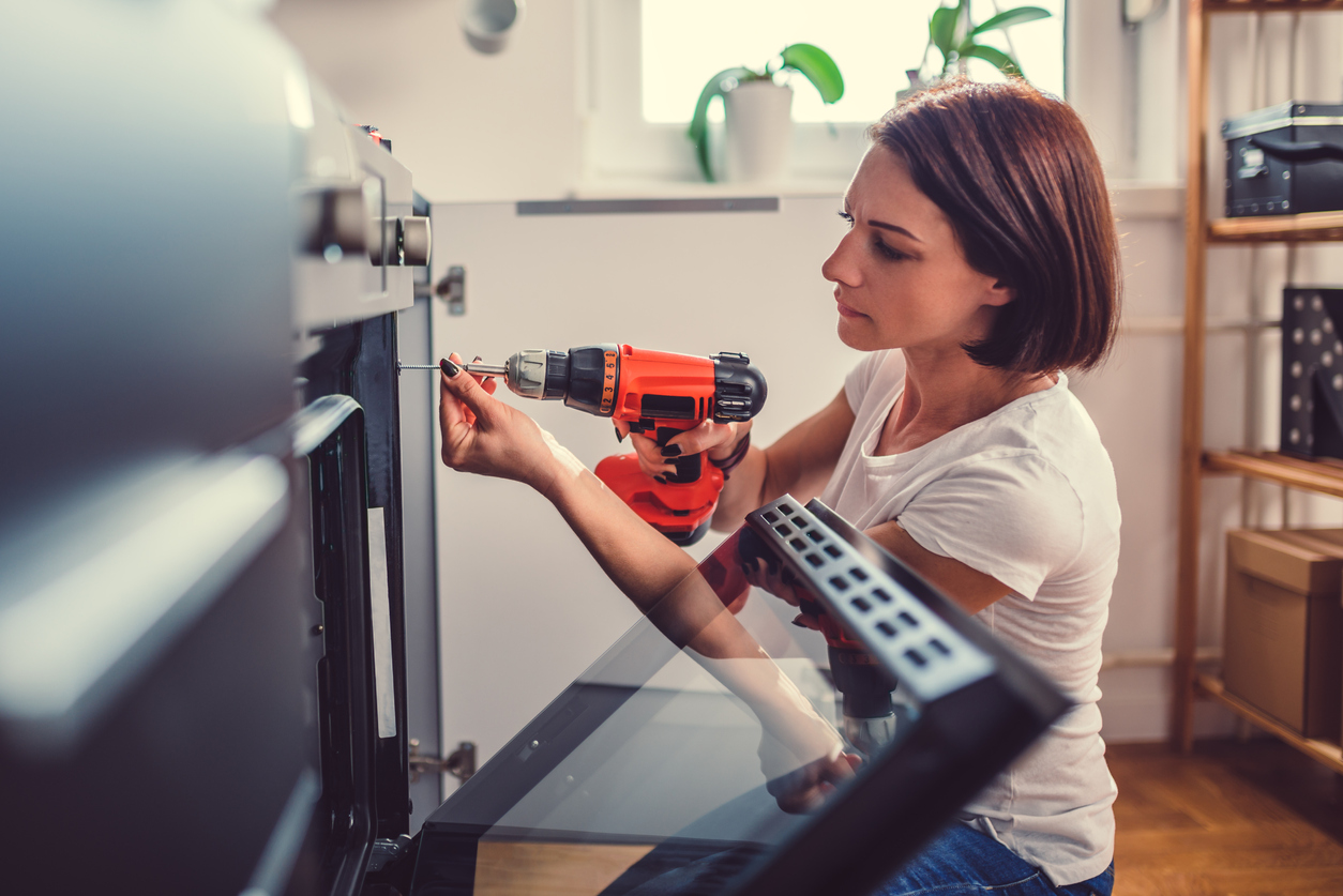 Woman working on a new kitchen installation and using a cordless drill