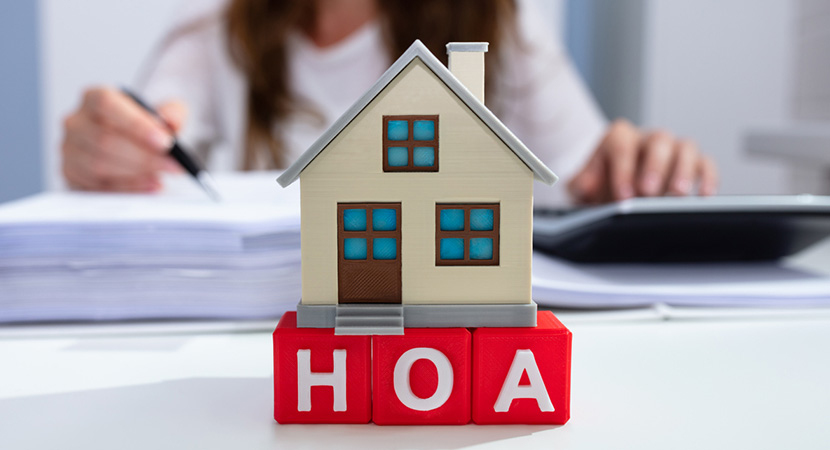 Tiny house on red letters that say HOA