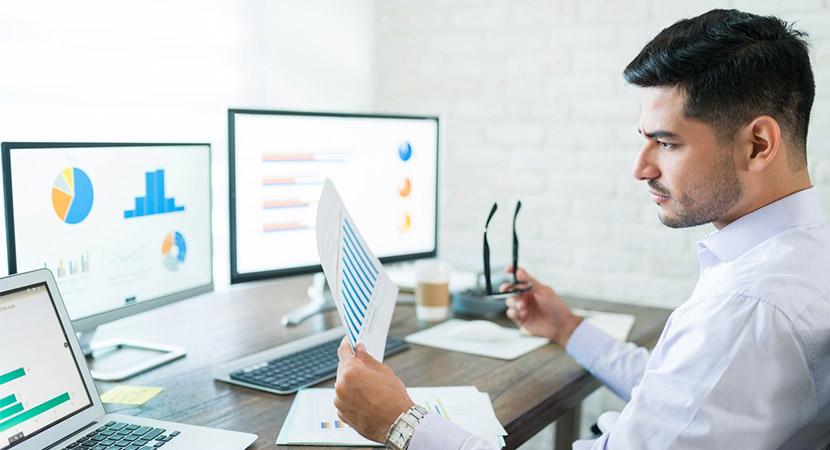 Man at computer looking at graphs