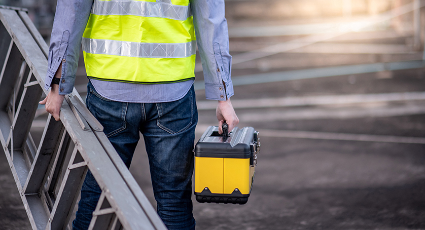 Maintenance worker man with safety helmet and green vest carrying aluminium step ladder and tool box at construction sit