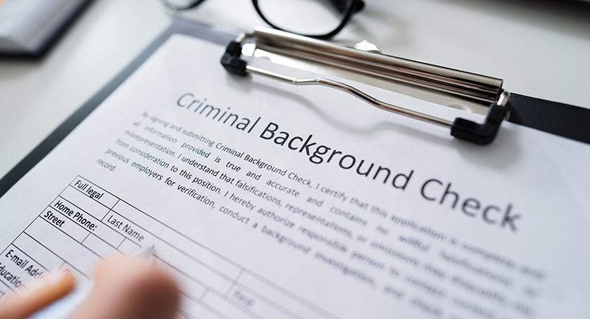 Close-up Of Human Hand Filling Criminal Background Check Application Form With Pen